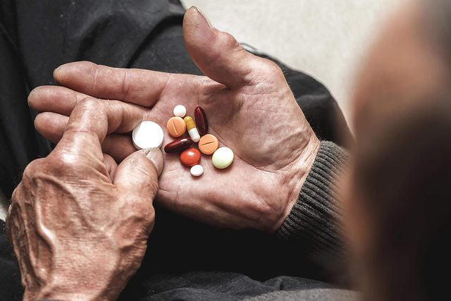 man with handful of medication