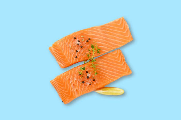 two fillets of salmon with pepper on top and a lemon wedge