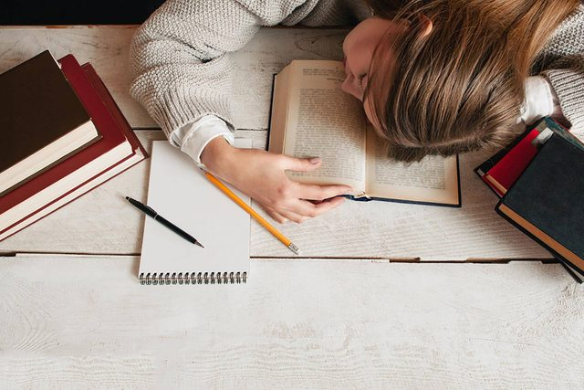 young woman asleep with head on books