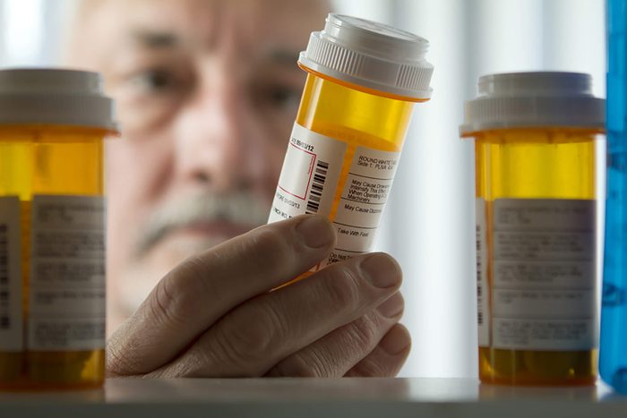Man looking into medicine cabinet, holding pill bottle