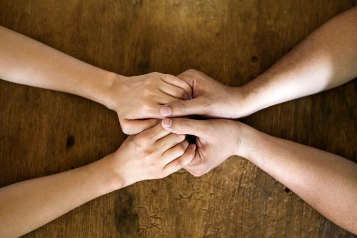 Close up on a couple hand holding hands on wooden table