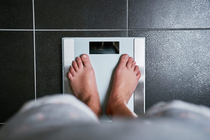 Female bare feet with weight scale, top view