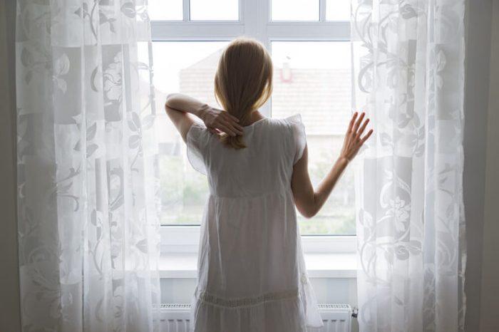 sad lady standing by a window
