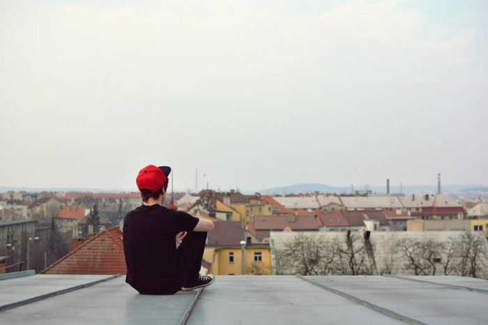 Young guy siting on the roof