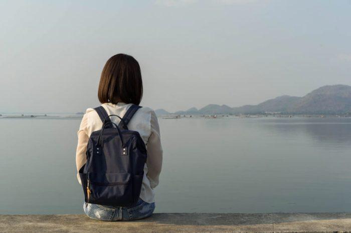 Behind the backpack Asian women on the Krasiew dam ,Dan chang Suphan Buri Thailand