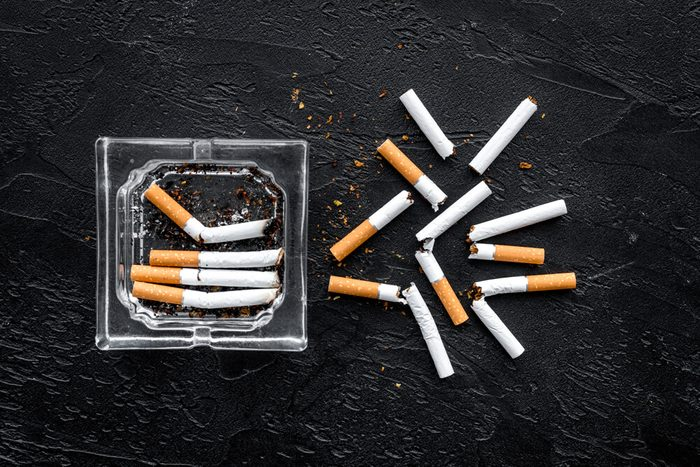 Smoking. Half-smoked cigarettes in ashtray on black background top view