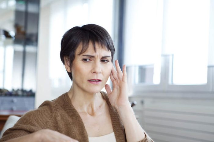 woman with a worried expression holding her hand to her ear