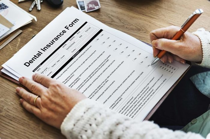 person filling out a Dental insurance form
