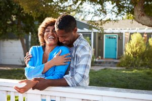 Mature black Couple Leaning On Back Yard Fence