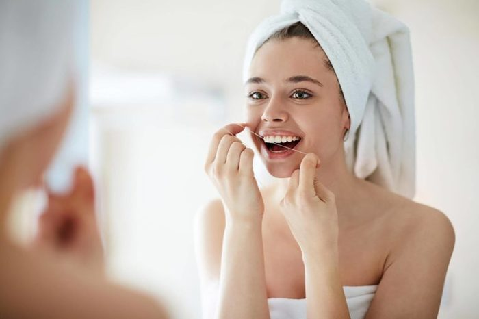 woman with towel around her hair flossing her teeth