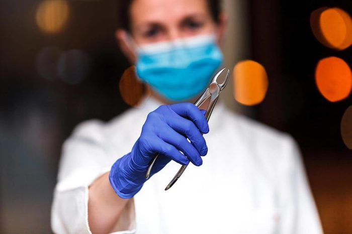 dentist looking into camera holding a tooth extractor