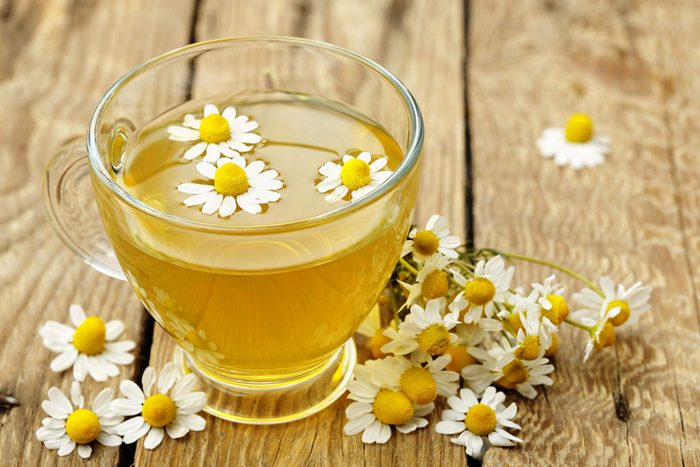 glass mug of chamomile tea topped and surrounded by chamomile flowers