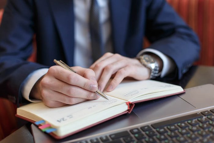 man writing in his planner book