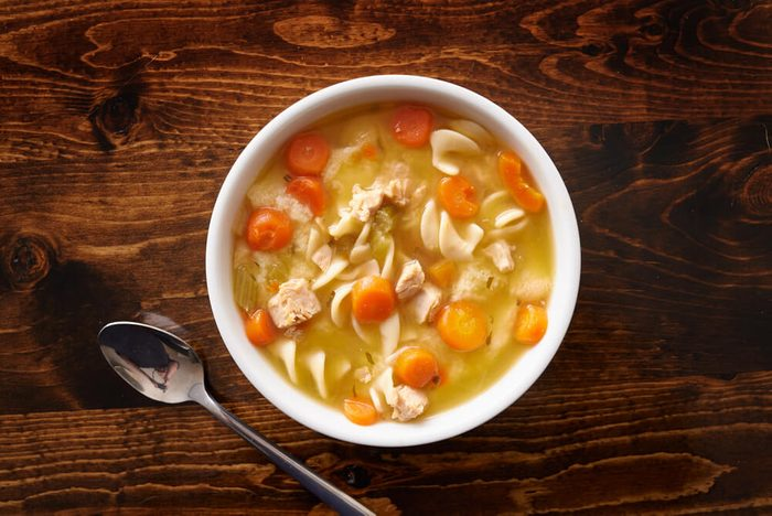 Heart healthy diet; bowl of chicken noodle soup shot top down