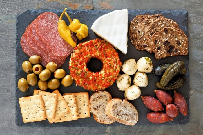 Appetizer platter with an assortment of cheeses, crackers, meats and snacks above view on a slate background