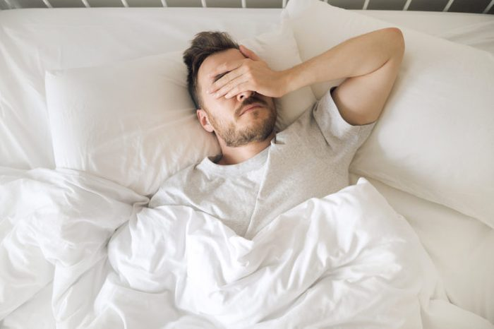 man suffering from insomnia overhead shot
