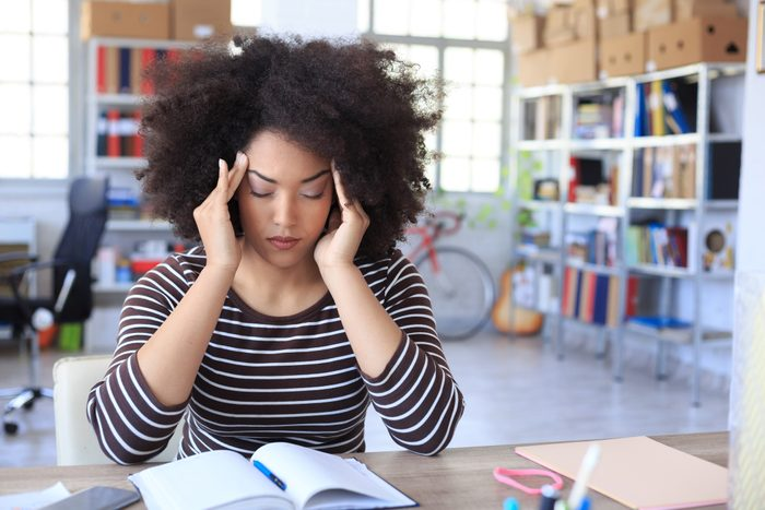 woman with headache pain at work