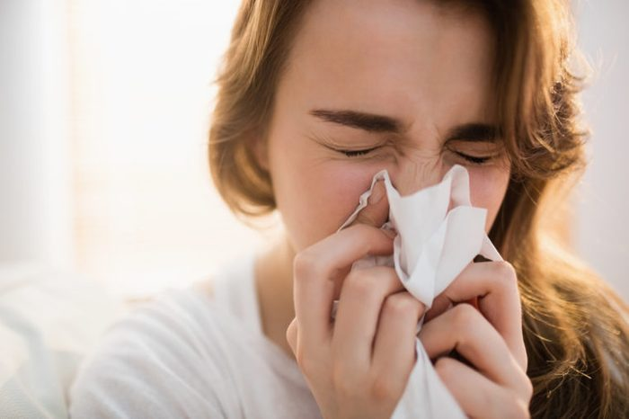 girl with runny nose blowing her nose into tissue