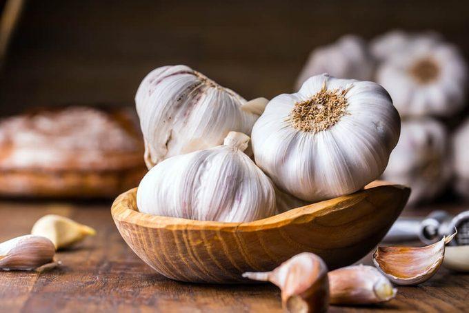 Garlic Cloves and Garlic Bulb in vintage wooden bowl.