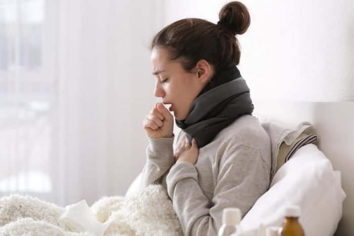 Young ill woman in bed at home.