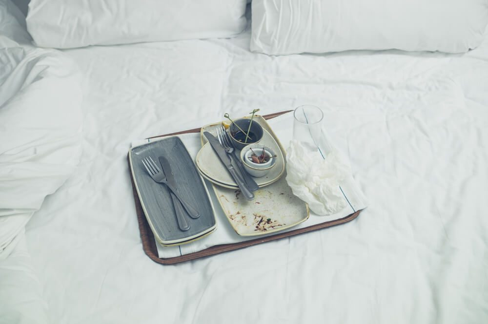 Dirty plates with leftover food on a bed