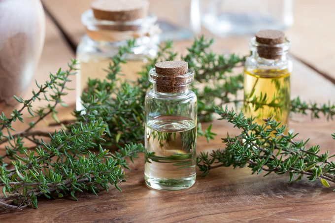Essential oils, herbs, glass bottles on a wood table