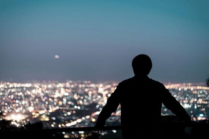 man on a balcony at night staring at city skyline