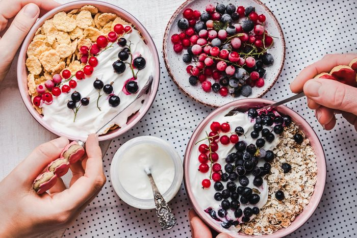 bowls of yogurt, berries, and cereal