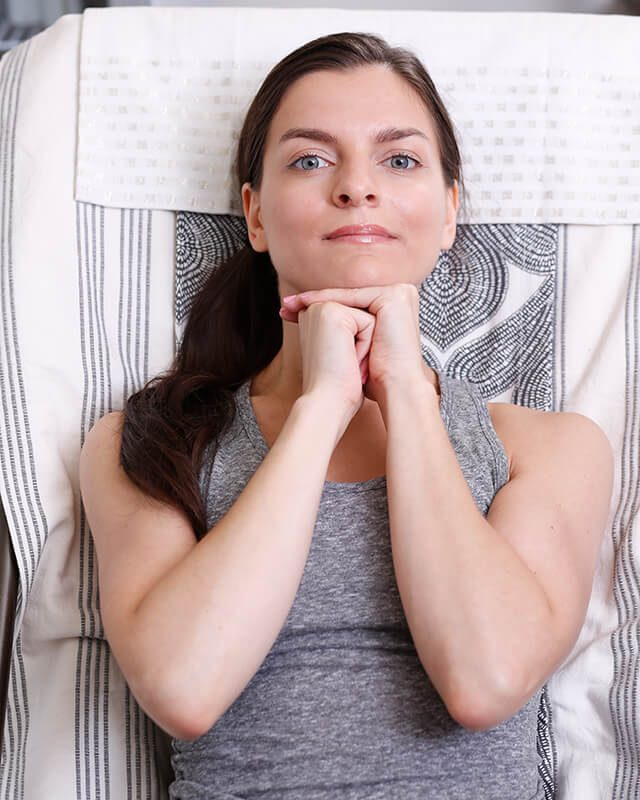 Woman doing facial exercises on her chin to improve her skin.