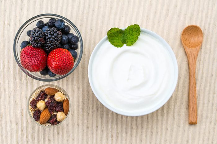 Bowl of Greek yogurt with berries and nuts on the side.