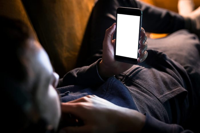 man on couch looking at phone