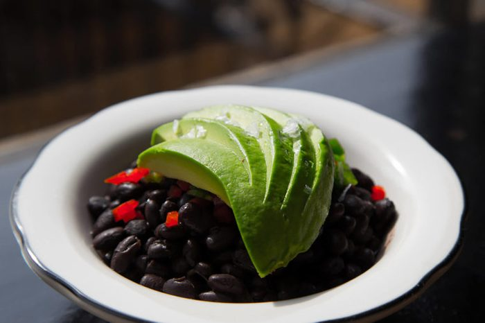 Black bean bowl topped with avocado slices.