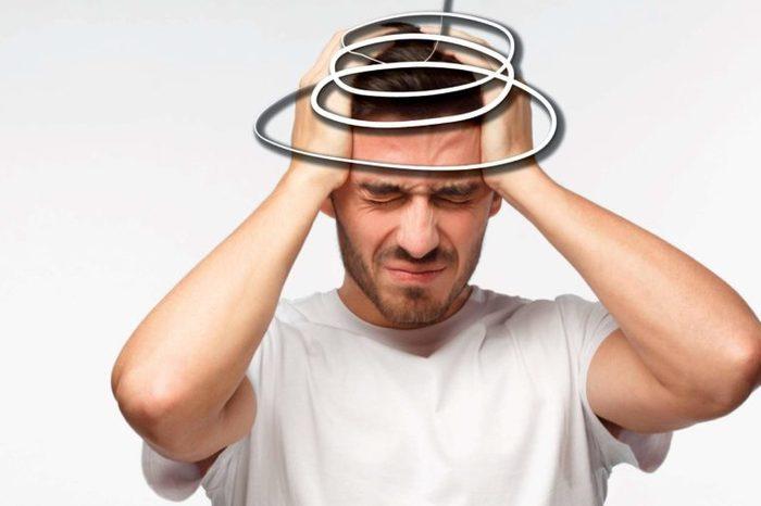man pressing against his head