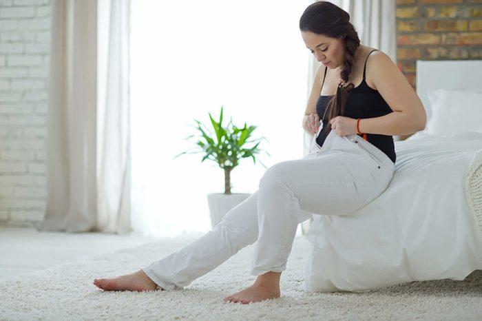 Woman-putting-on-pants