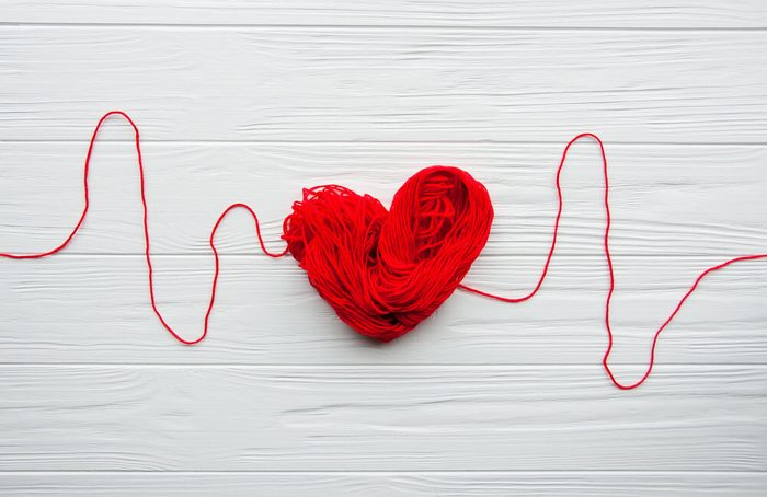 Heart and cardiogram made of red thread.