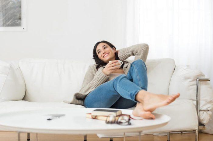 Young smiling woman sitting on sofa and looking up while drinking hot tea. Young brunette woman thinking at home in a leisure time. Happy girl relaxing at home on a bright winter morning.