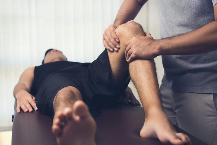 therapist massaging knee of male patient