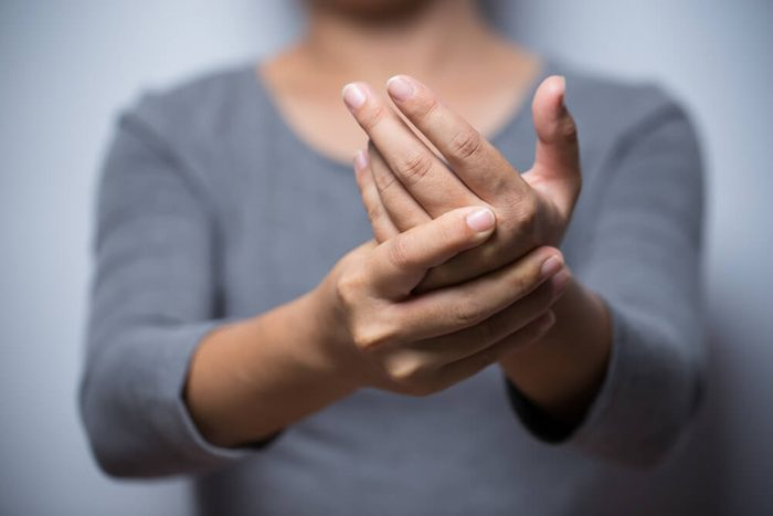 Woman holding wrist with hand pain