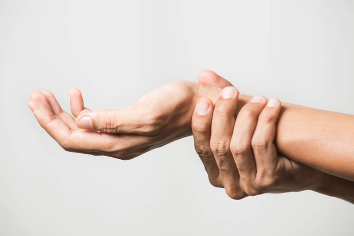 person holding wrist, hand pain