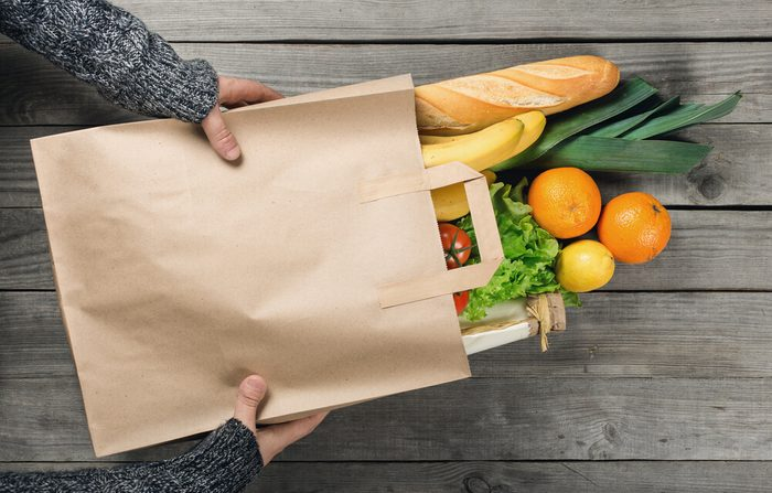 hands holding paper bag of groceries including vegetables, fruit and bread