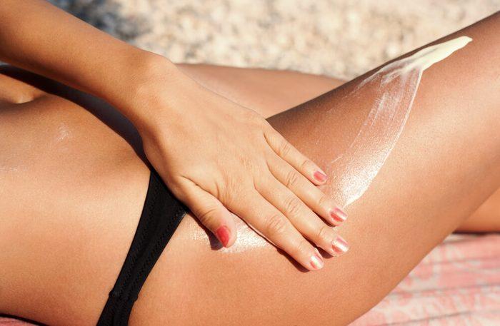 woman applying sunscreen on leg