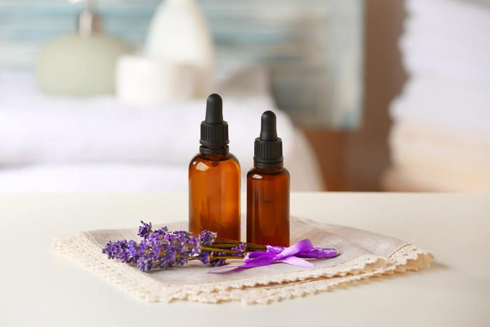 Bottles of essential oil with lavender on table