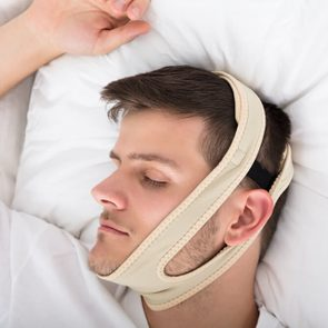 Young Handsome Man Sleeping With Anti Snoring Chin Strap On Head At Home