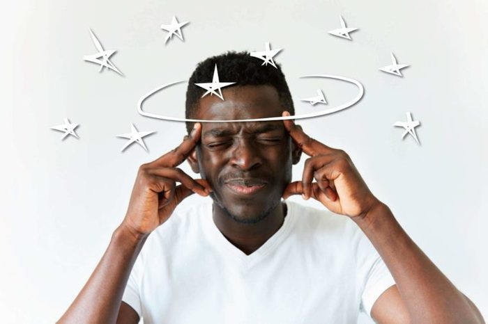 Black man squeezing his eyes shut and holding his temples