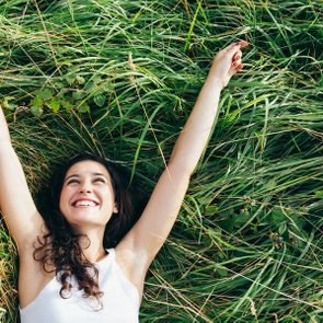 Young happy woman laughing in a bed of grass with arms outstretched