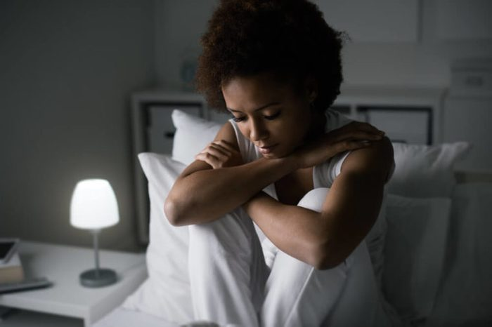 Sad depressed woman sitting in her bed late at night