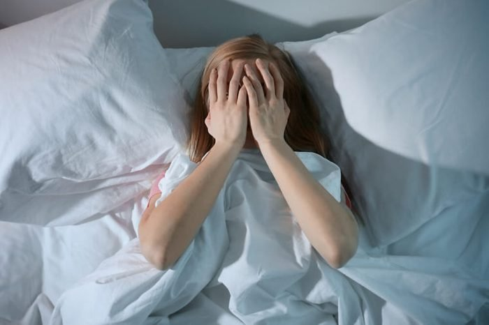 Young scared woman lying in bed with her hands over her face