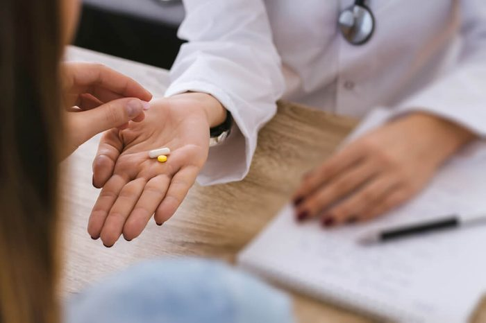 Female nurse give pill to young patient