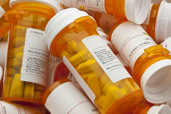 Bottles of prescription medicine in a pile. This collection of pill containers is symbolic of the many medications senior adults and chronically ill people take.