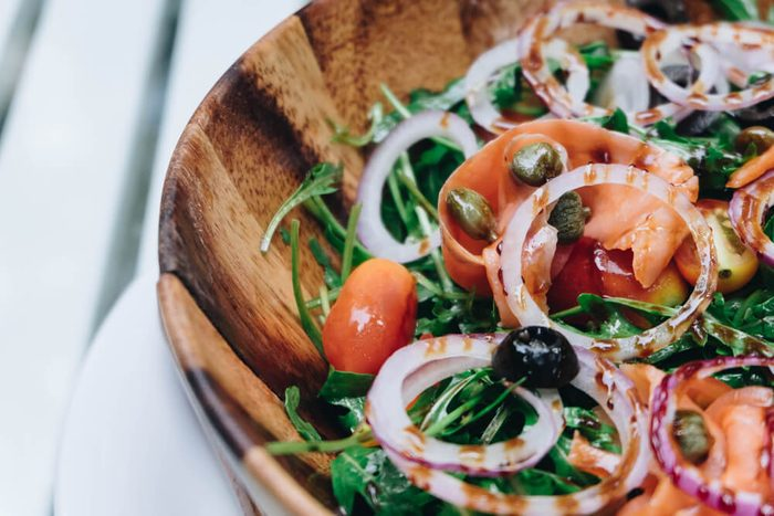 Smoked salmon salad with red onion, capers, lemon and arugula.and green rocket